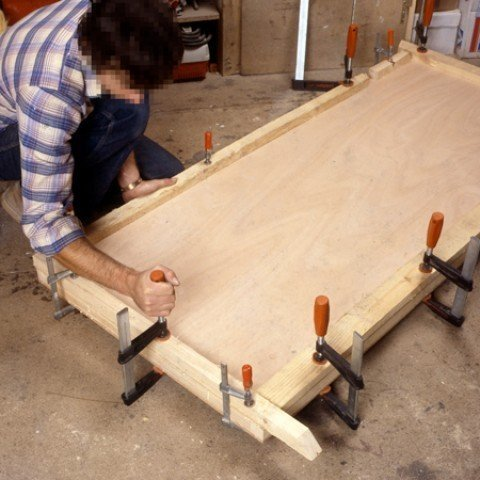Gently lay the second plate on the glued frame. Be careful, the glass wool should not exceed the frame cleats. Hold the door firmly using clamps.