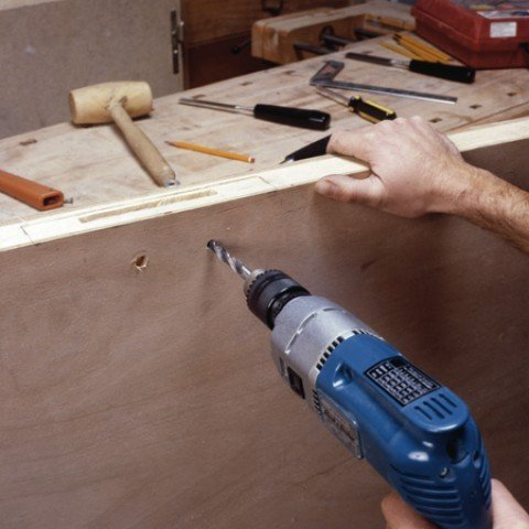 """Identify the holes to be drilled for the passage of the key (called """"entry barrel"""") and for the lever handle lock. Drill well perpendicular to the lock."""